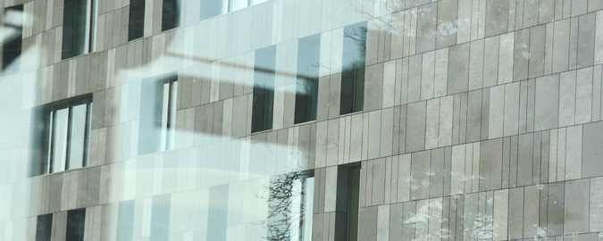 This photograph of a modern building seen through a pane of glass that reflects light and tree branches illustrates this page about RealCorp Luxembourg Clients