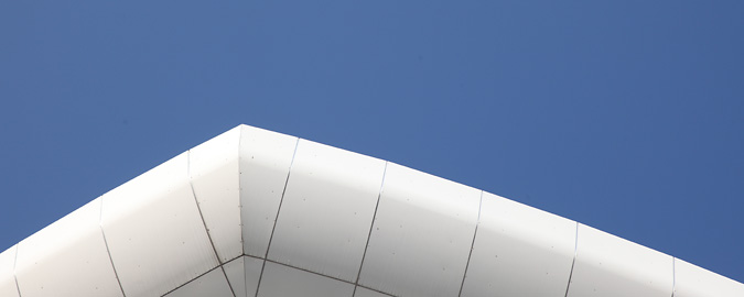 Abstract view of the bevelled edge of a modern white building roof to sky beyond symbolises a graph tracking capital markets activity