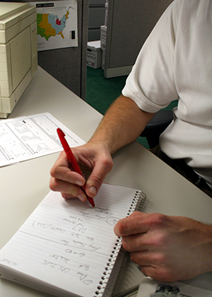 A person writing on a notepad, as a commercial real estate valuer notes down his observations before calculating a value
