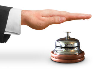 Man's suited hand hovering over service bell representing access to RealCorp Luxembourg's commercial real estate services