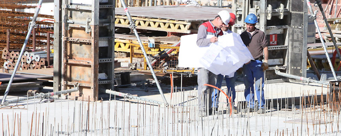 Hardhatted builder on a construction site consulting a large plan symbolising the consulting of RealCorp's commercial real estate resources