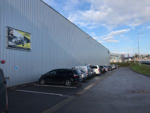 RealCorp Luxembourg brokered this lease of an industrial warehouse in Contern. The image shows a white corrugated wall of the warehouse with a small window in the foreground and several cars parked in demarcated parking bays on tarmac alongside the wall. The sky is blue with some grey clouds and there is a view of grass in the distance to the right of the tarmac.