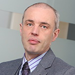 Headshot against a light grey background of Laurent Pedrini, Associate Director - Occupier Markets, RealCorp Luxembourg. Laurent wears a grey suit, dark tie and striped shirt. His greying hair is close-cropped. He is looking directly at the camera.