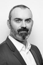 Portrait en noir et blanc de la tête et des épaules de M. Laurent Cooreman de SQUARE METER : Un homme au front haut, aux sourcils foncés, à la moustache et au bouc foncé qui se fond dans une barbe grise. Il porte une chemise blanche avec un col déboutonné et une veste noire.