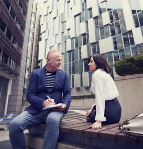 mand and woman in conversation seated on a concrete bench in front of tall glass-fronted commercial buildings.
