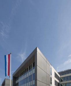 An upward shot of the top floor of one of the IKAROS 2.0 Luxembourg buildings. The top corner points into a high blue sky. Alongside it is the Luxembourg flag, hanging vertically from a tall flagpole.