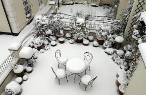"In a snowy low-walled garden, a small round table and four French ironwork chairs each carry a perfectly round thick ""slice"" of snow. Undisturbed, they are placeholders for the human presence that will result from your property search."