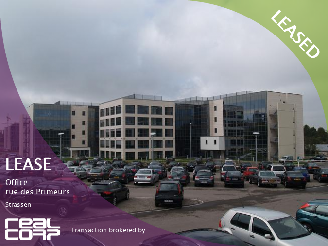 RealCorp Luxembourg LEASED to HeidelbergCement Finance Luxembourg sàrl this Office in rue des Primeurs, Strassen.  The image shows a five-storey building with cream-coloured walls dominated by large regular windows in dark glass. In front of the building is a large car park filled with cars.